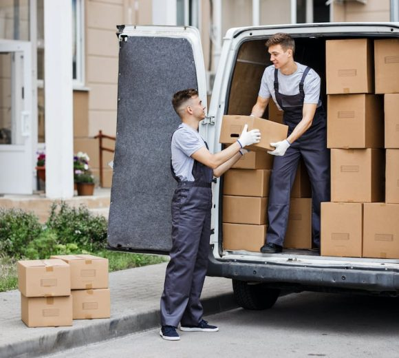 two-young-handsome-movers-wearing-uniforms-are-unl-LVNB42S.jpg